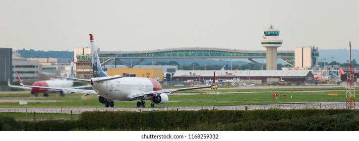 GATWICK AIRPORT, ENGLAND, UK – AUGUST 30 2018: Norwegian Airlines planes prepare to take off from Gatwick Airport overlooked by the air traffic control tower and aeroplane bridge.