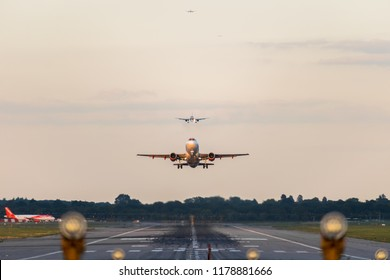 GATWICK AIRPORT, ENGLAND, UK – SEPTEMBER 13 2018: View directly down the runway as an easyJet Airlines plane takes off from Gatwick Airport with planes coming in to land behind it in the background.