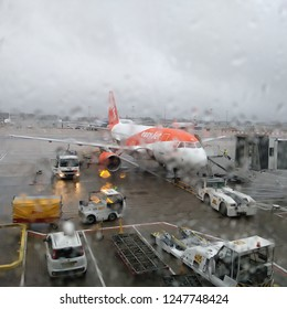 Gatwick Airport, London, UK - 12/01/2018: EasyJet airplane being prepared for boarding and takeoff seen through a wet window during a rainy day