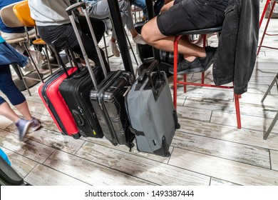 Gatwick, London / UK - 18 Aug 2019: Travellers sit on red bar stools while waiting for flights. Four carry on luggage cases are lined up, coloured red, grey and black; someone walks past in a blur.