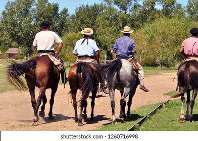 Gauchos dressed up in traditional outfits riding horses in Argentina