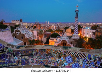 Gaudi bench and cityscape of Barcelona from park Guell illuminated at blue night, Spain