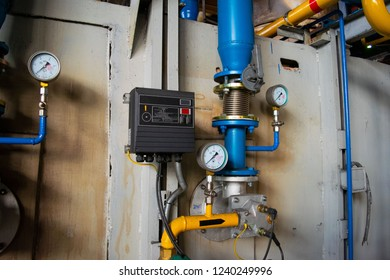 Gauges in the boiler room near the heating pipes with insulation coating. Electric power meter measuring power usage. Watt hour electric meter measurement tool. oil and gas pipeline