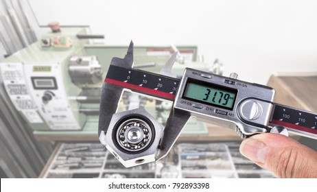 Gauging of ball bearing by digital caliper. Accurate measuring tool and blurred workroom with a lathe on the background.