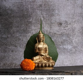Gautama Buddha statue against the background of the pipal leaf