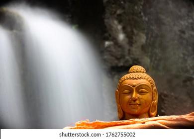 Gautama Buddha statue near waterfall, peace and meditation.