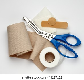 Gauze, ace bandage, tape, scissors and bandages shot on white background with a soft shadow