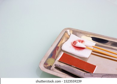 Gauze,blood,scissors,roll gauze ,plaster and two swab cotton bus sticks in medical surgical tray and copy space