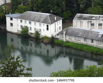 Gave de Pau river flowing through Lourdes with the town's buildings by the river bank. Hautes-Pyrenees, Occitanie, Southwest France