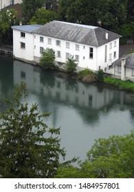 Gave de Pau river flowing through Lourdes with a town's building by the river bank. Hautes-Pyrenees, Occitanie, Southwest France
