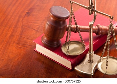 Gavel, ancient bronze scales and law book on the table