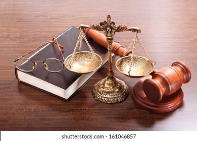Gavel, antique scales, book and glasses on a varnished wooden table