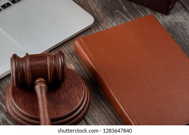 Gavel, book and laptop on wooden table in a lawyer office. Jurisprudence concept.