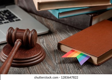 Gavel, a book with a rainbow bookmark. LGBT agenda in jurisprudence, rights and justice.