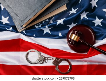 Gavel, books and handcuffs over american flag