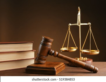 Gavel with books and scales on brown background