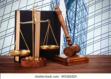 Gavel with books and scales on modern skyscraper background