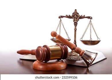 Gavel, bronze scales, a book and a bell on the table
