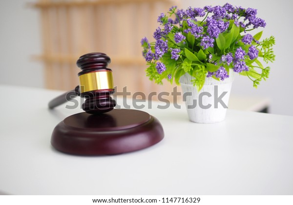 Gavel and dry flower on table. A hammer for judges to judge the case is both right and wrong. Or may be used as a device to use the auction. To judge the winners.