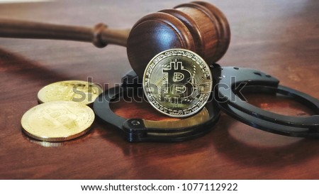 Gavel and handcuffs with bitcoins on wooden desk. Cryptocurrency legal concept.
