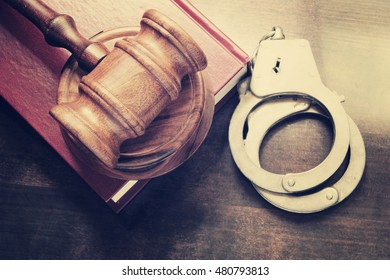 Gavel and handcuffs with red legal book on wooden table