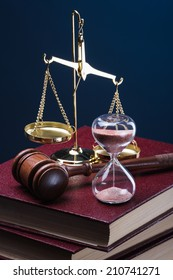 gavel, hourglass and book on blue background
