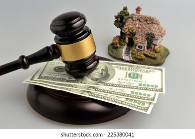 Gavel of judge with dollars and model of house on gray background