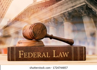 gavel judge with federal law books on desk of lawyer with court background.