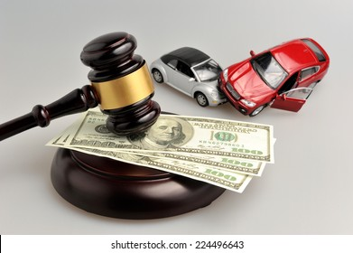 gavel judge with money and toy cars on gray background