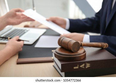 Gavel with juridical books on table in lawyer's office