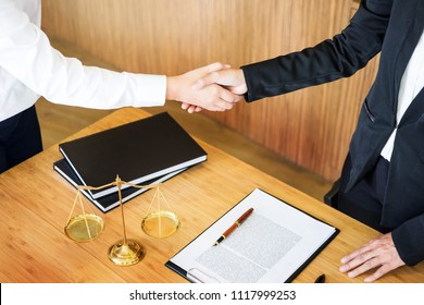 Gavel Justice hammer on wooden table with judge and client shaking hands after adviced in background at courtroom, lawyer service concept