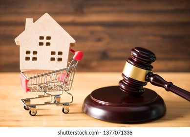 gavel justice hammer and wood house in shopping cart, house auction