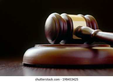 Gavel laying on its side on sounding block on black background