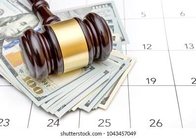 Gavel with money on the calendar.