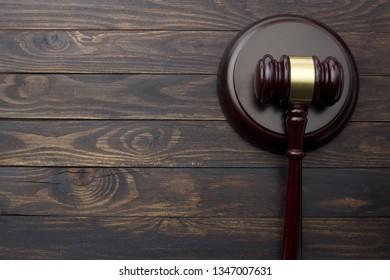 Gavel on dark wooden background. Low light.