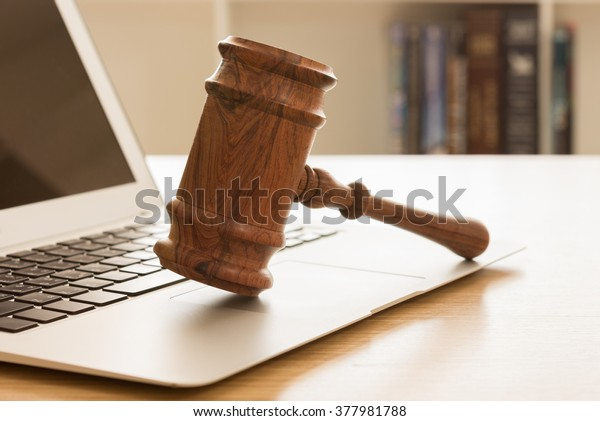 Gavel on keyboard laptop computer. Concept of On-line auction.