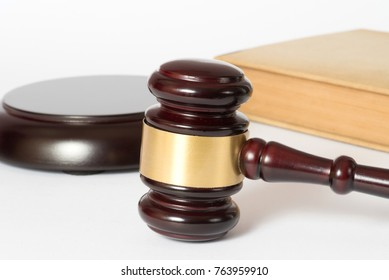 A gavel on a white background and a law book