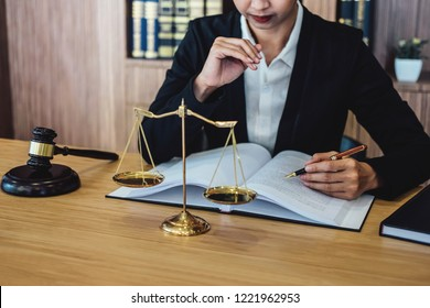 Gavel on wooden table and female Lawyer or Judge working with agreement in Courtroom theme, Justice and Law concept.