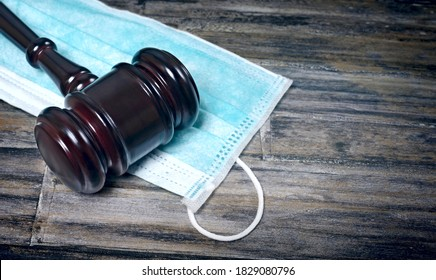 Gavel Resting On A Protective Mask on a wooden table.