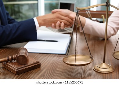Gavel, scales and blurred lawyer handshaking with client on background