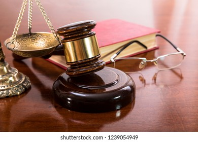 Gavel, scales, book and glasses on the table
