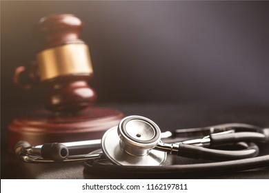 Gavel and stethoscope on wooden background, symbol