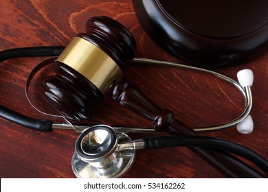 Gavel and stethoscope on a wooden surface.