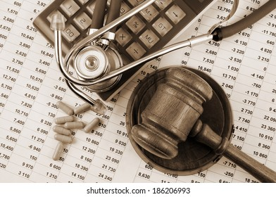 Gavel, stethoscope and pills on financial document