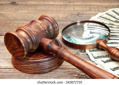 Gavel, USA Dollars and Vintage Magnifying Glass on Grunge Wood Table