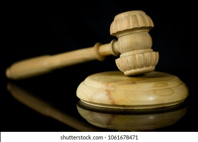 Gavel, wooden judge hammer with sound block on the black mirror background, hammer of a judge.