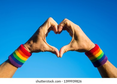 Gay athlete making hand heart with gay pride rainbow colors sport wristbands against bright blue sky