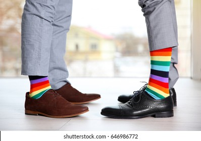Gay couple with colorful socks on light floor