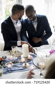 Gay Couple Cutting Cake Together on Wedding Reception