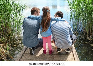 Gay couple with daughter on a pier